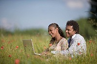 Mixed race couple with laptop in field of flowers