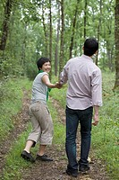 Asian couple walking down path holding hands