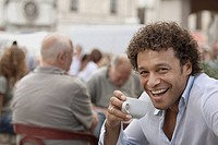 Mixed race man drinking coffee at sidewalk cafe