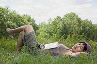 Asian woman laying in grass with book