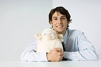 Young man hugging stuffed toy, smiling at camera