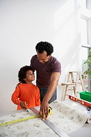 African father showing son how to measure wallpaper