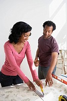 African couple measuring wallpaper (thumbnail)