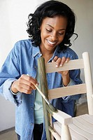 African woman painting rocking chair