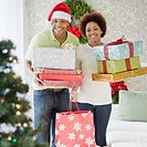 African couple holding stacks of Christmas presents