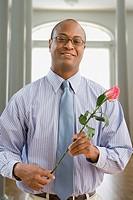 African man holding pink rose