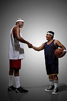 Tall basketball player shaking hands with short basketball player