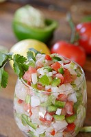 Close-up of large glass filled with Ceviche. Lemon, pepper &amp; tomatoes in background