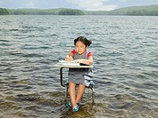 A girl sat at a desk in a lake