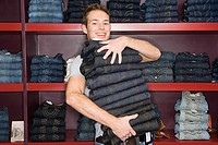Man holding a stack of jeans