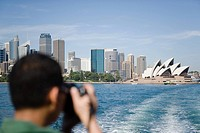 A tourist photographing sydney opera house
