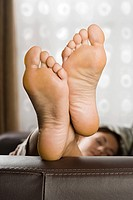 Feet of woman on sofa