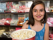 Girl holding a tub of popcorn
