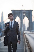 Businessman walking across brooklyn bridge
