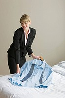 A woman laying a suit out on a bed