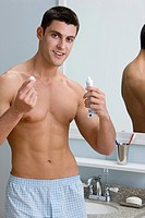 A man holding a tube of toothpaste and lid