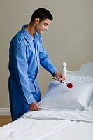 A man putting a rose on a pillow