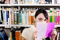 Young woman in library with book (thumbnail)