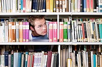 Student looking though bookshelf