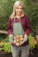 Smiling woman holding potatoes