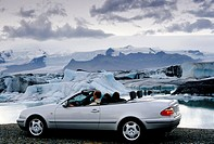 A couple sitting in a silver Mercedes Convertible with open deck in front of a glacial lake, Joekulsárlón at the foot of the Vatnajoekull, Iceland, Eu...