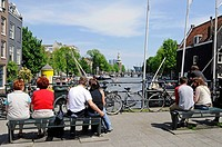 Street scenery, people sitting on benches, bridge, canal, Amsterdam, Holland, Netherlands, Europe