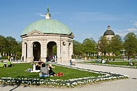 People enjoying the warm spring day in front of the pavilion for the goddess Diana in the Hofgarten, Munich, Bavaria, Germany, Europe