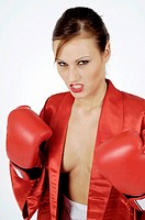 Boxing, young woman dressed in a scant silk robe posing aggressively, bearing her teeth and clenching her gloved fists
