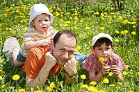 Father, Gaudenz Huggel, and his two sons lying on a dandelion meadow, Arlesheim, Baselland, Switzerland