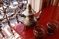 Ornate Moroccan teapot and glasses on a red table in the historic Medina quarter, Marrakesh, Morocco, Africa