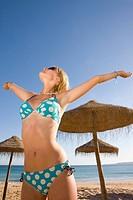 Stylish teenage girl posing on beach