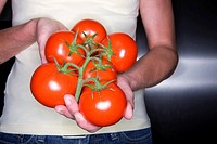 Close up of woman holding fresh tomatoes
