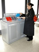 Recycling unit. Woman disposing of her newspaper at a recycling unit. This unit contains bins for disposing of plastic bottles red, cans grey, paper b...
