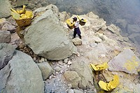 Sulphur workers, Kawa Ijen, Ijen Plateau, East Java, Indonesia. Sulphur workers collecting sulphur rocks from volcano