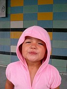 Spontaneous portrait of a 4 year old girl with hooded pink dress in front of colored tile wall at the swimming pool. The girl is half Japanese and hal...