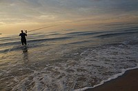 Man fishing at sunrise on Malvarrosa beach, Valencia city, Valencia, Comunidad Valenciana, Spain, Europe