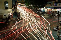 Chaotic traffic is illustrated by the streaking lights in this time exposure of a busy intersection in the Old Quarter, Hanoi, Vietnam