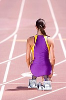 Female runner at starting block kneeling on race track