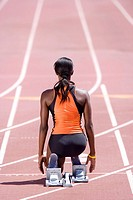 African female runner at starting block kneeling on race track