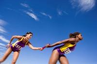 Female athletes passing relay race baton