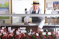 Butcher in uniform behind meat counter