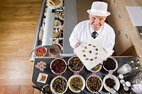 Sales clerk displaying specialty olives