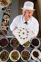 Sales clerk displaying specialty olives