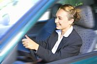 Happy businesswoman driving car