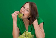 young woman eats grapes