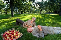 Mature couple on grass by basket of apples, woman smiling