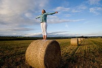Teenage girl 16-18 standing on bale of hay in field with arms outstretched (thumbnail)