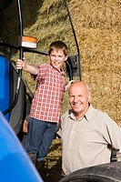 Portrait of farmer and grandson near tractor and hay