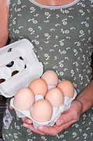 Close up of woman holding half dozen brown eggs