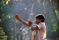 Tribal boy with stone arrow and bow Jenu Kurumba , Nagarhole , Tamil Nadu , India